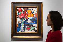 "© Licensed to London News Pictures. 18/11/2016. London, UK. A staff member views ""Still Life With Tulips and Oranges"" by Samuel John Peploe (est. GBP250-350k), at the preview at Sotheby's of works on view at four upcoming November auctions featuring Modern & Post-War British Art, A Painter's Paradise (Julian Trevelyan & Mary Fedden at Durham Wharf), Scottish Art and Picasso Ceramics from the Lord & Lady Attenborough Private Collection. Photo credit : Stephen Chung/LNP"