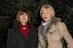 © Licensed to London News Pictures. 08/12/2014. London, UK. Helen Mirren with local councillor for Wapping and St Katharines, Denise Jones. Dame Helen Mirren turns on the Christmas tree lights at Wapping Green in Tower Hamlets, East London tonight. This is the first time in many years that Wapping has had a Christmas tree and Dame Helen Mirren surprised residents by turning up at the community event and leading the countdown to switching the tree lights on. She then joined residents singing carols and drinking mulled wine, at the event which was arranged by the local councillor for Wapping and St Katharines, Julia Dockerill. Photo credit : Vickie Flores/LNP