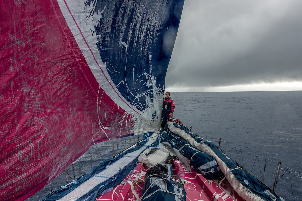 November 25, 2014. Leg 2 onboard Team SCA. Stacey Jackson helps hoist the J1 as we are surrounded by rain clouds.