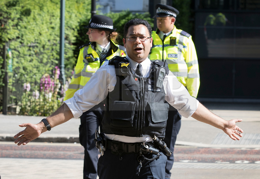 © Licensed to London News Pictures. 06/06/2018. London, UK. A policeman shouts for people to move away from the back of the Mandarin Oriental hotel during a fire. Fifteeen fire engines and 97 firefighters and officers have been called to a fire believed to be at the Mandarin Hotel in Kightsbridge. Photo credit: Peter Macdiarmid/LNP