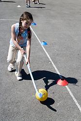 Girl playing hockey in school playground,