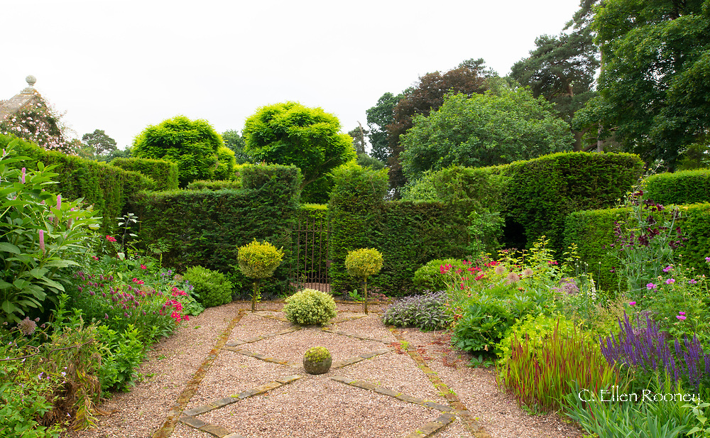 Herbaceous borders around a brick and gravel path in the Bishop's Garden at Cothay Manor, Greenham, Wellington, Somerset, UK