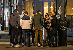 © Licensed to London News Pictures. 25/09/2020. London, UK. People gather in a group larger than six after leaving a bar on Portobello Road in Notting Hill, west London, at 10pm when a curfew comes in to place as part of new restrictions intended to prevent the spread of COVID-19. Photo credit: Ben Cawthra/LNP