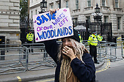 An activist from HS2 Rebellion, an umbrella campaign group comprising longstanding campaigners against the HS2 high-speed rail link as well as Extinction Rebellion activists, holds a sign outside Downing Street calling for England's ancient woodlands to be saved on 4 September 2020 in London, United Kingdom. A rally was held by HS2 Rebellion in Parliament Square as well as direct action at the Department of Transport during which activists glued themselves to the doors and pavement outside and sprayed fake blood around the entrance in protest against the high-speed rail link.