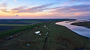 Nederland, Zeeuws-Vlaanderen, Nieuw-Namen, 05–11-2020; Emmadorp, Het Verdonken Land van Saeftinghe,  getijdengebied in het oosten Zeeuws-Vlaanderen op de grens met Belgie en onderdeel van het estuarium van de Schelde.Speelmansgat.  De voormalige polder is het grootste brakwatergebied van Europa en staat onder invloed van het getij. Het Verdronken Land is een natuurreservaat, in beheer bij het Zeeuws Landschap en belangrijk als broed-, overwinterings- en rustgebied voor vogels. <br /> The Drowned Land of Saeftinghe, tidal area in the east of Dutch Flanders on the border with Belgium. The former polder is the largest brackish water of Europe and because of the the tides, there are mud flats and gullies. The Drowned Land is a nature reserve, not freely accessible. It is managed by the Zeeuws Landscape and important as bird sanctuary, part of the Scheldt estuary.<br /> drone-opname (luchtopname, toeslag op standaard tarieven);<br /> drone recording (aerial, additional fee required);<br /> copyright foto/photo Siebe Swart