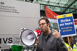 London, UK. 15 July, 2019. Sam Gurney, TUC Regional Secretary for London, East & South East England, addresses catering and cleaning staff belonging to the PCS trade union and outsourced to work at the Department for Business, Energy and Industrial Strategy (BEIS) via contractors ISS World and Aramark on the picket line outside the Government department after walking out on an indefinite strike for the London Living Wage, terms and conditions comparable to the civil servants they work alongside and an end to outsourcing.