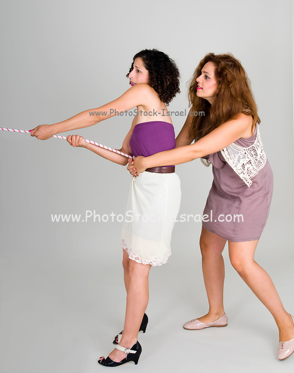 Team work one young woman pulls on another woman that is pulling a rope
