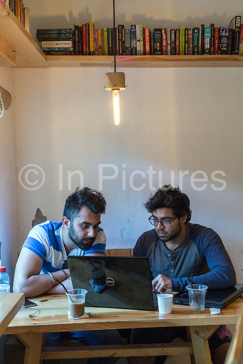 A couple working at the JugMugThela shop in Champa Gali, New Delhi, India. Champa Gali is the latest and most intimate of Delhis urban creative villages.