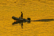 A boater is silhouetted as he rides his dinghy across Boothbay Harbor at sunset during summer in Boothbay Harbor, Maine.