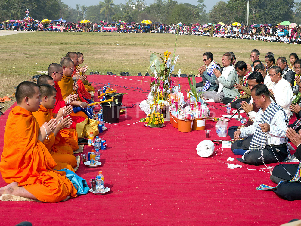 Buddhist monks and important local dignitaries during the baci ceremony at the Sayaboury elephant festival, Sayaboury province, Lao PDR. The baci is a long series of chanted blessings and exhortations to welcome back any 'kwans' or body spirits that might have been lost. In traditional Lao culture it is believed that elephants, like humans, have 32 kwan (or souls), vital for health and spiritual wellbeing.<br /> <br /> Originally created by ElefantAsia in 2007, the 3-day elephant festival takes place in February in the province of Sayaboury with over 80,000 local and international people coming together to experience the grand procession of decorated elephants. It is now organised by the provincial government of Sayaboury.The Elephant Festival is designed to draw the public's attention to the condition of the endangered elephant, whilst acknowledging and celebrating the ancestral tradition of elephant domestication and the way of life chosen by the mahout. Laos was once known as the land of a million elephants but now there are fewer than 900 living in the country. Around 470 of them are in captivity, traditionally employed by a lucrative logging industry. Elephants are trained and worked by a mahout (handler) whose relationship to the animal is often described as a marriage and can last a lifetime. But captive elephants are often overworked and exhausted and as a consequence no longer breed. With only two elephants born for every ten that die, the Asian elephant, the sacred national emblem of Laos, is under serious threat of extinction.