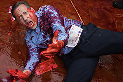 An environmental activist from Extinction Rebellion dressed as a financier covers himself in fake blood in Paternoster Square following a Blood Money March through the City of London on 27th August 2021 in London, United Kingdom. Extinction Rebellion were intending to highlight financial institutions funding fossil fuel projects, especially in the Global South, as well as law firms and institutions which facilitate them, whilst calling on the UK government to cease all new fossil fuel investment with immediate effect.