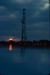 Stock photo of an on-shore rig reflecting in the water at a foggy sunrise