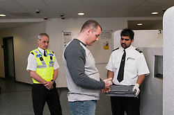 Suspect being searched at charge desk in Middlesborough police station