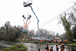 Bailiffs abseil from a large cherry picker towards Dan Hooper, widely known as Swampy during the 1990s, who is sitting on a bamboo tripod positioned in the river Colne on 8th December 2020 in Denham, United Kingdom. The climate and roads activist had occupied the tripod the previous day in order to delay the building of a bridge as part of works for the controversial HS2 high-speed rail link and a large security operation involving officers from at least three police forces, National Eviction Team enforcement agents and HS2 security guards was put in place to facilitate his removal.