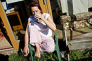 Tasha Burrage, 20, is portrayed while smoking a cigarette in front of her house in BedZED on Thursday, Sep. 6, 2007. BedZED or the Beddington Zero Energy Development, is an environmentally-friendly housing development near Wallington, England in the London Borough of Sutton. It was designed by the architect Bill Dunster who was looking for a more sustainable way of building housing in urban areas in partnership between the BioRegional Development Group and the Peabody Trust. There are 82 houses, 17 apartments and 1,405 square meters of work space were built between 2000. The project was shortlisted for the Stirling Prize in 2003. The project is designed to use only energy from renewable source generated on site. In addition to 777 square meters of solar panels, tree waste is used for heating and electricity. The houses face south to take advantage of solar gain, are triple glazed and have high thermal insulation while most rain water is collected and reused. Appliances are chosen to be water efficient and use recycled water wherever possible. Low impact building materials were selected from renewable or recycled sources and were all originating within a 35 mile radius of the site to minimize the energy required for transportation. Also, refuse collection facilities are designed to support recycling and the site encourage eco-friendly transport: electric and LPG cars have priority over petrol/diesel cars, and electricity is provided by parking spaces appositely built for charging electric cars.