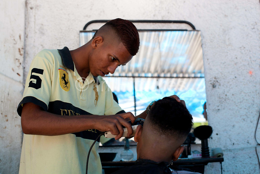 Boy young man having his hair cut into a street style. Young independent barber shop hair stylist in the street for the young people guys of Vila Valquiere, West Zone Zona Oueste, Rio de Janeiro