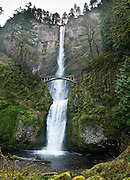 Multnomah Falls plunges 620 feet in two tiers in Columbia River Gorge National Scenic Area, adjacent to Interstate 84 and Historic Columbia River Highway, in Oregon, USA. A foot trail leads to Benson Footbridge, a 45-foot (14 m) long footbridge that allows visitors to cross 105 feet (32 m) above the lower cascade. Panorama stitched from 5 overlapping images.