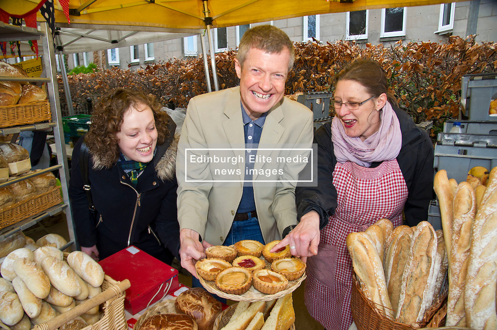 Pictured: Willie Rennie holding a tray of French tarts in the centre with Hannah Betsworth (L) chatted and stallholder Sara Roseburgh(r)<br /> <br /> Liberal Democrat leader Willie Rennie and  Hannah Bettsworth, Liberal Democrat candidate for Edinburgh Central and the Lothian regional list, headed to Stockbridge today to meet Easter shoppers and stallholders at the Sunday farmers market. <br /> <br /> Ger Harley | EEm 27 March 2016
