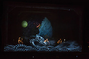 A sea monster is projected on a scrim in front of the Tiger Lilles.