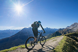 Mountain biker riding uphill in alpine landscape, Tyrol, Austria