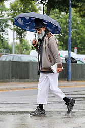 © Licensed to London News Pictures. 19/07/2019. London, UK. A man shelters from the rain beneath an umbrella in north London. Photo credit: Dinendra Haria/LNP
