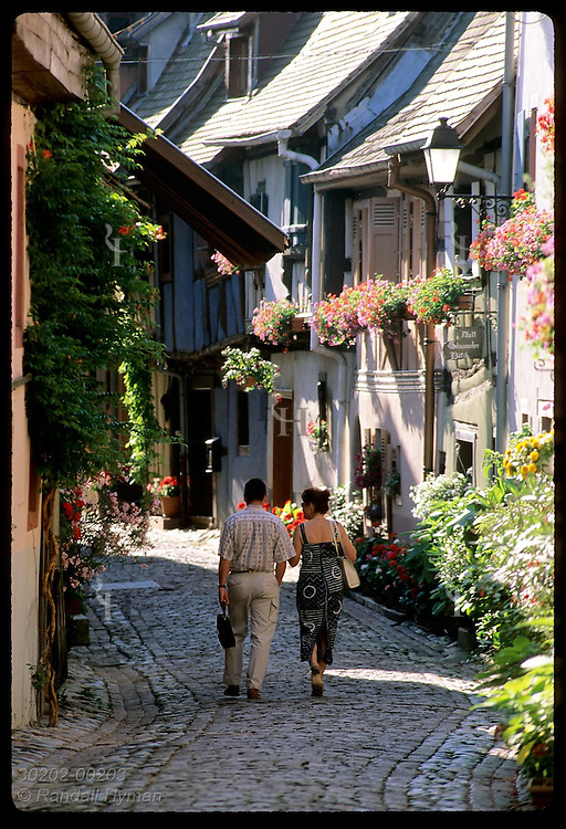 Couple walks down narrow street lined with half-timbered homes & flowers; (v) Eguisheim, Alsace France