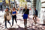 Een vrouw in een blauwe strakke rok loopt over Market Street in San Francisco. De Amerikaanse stad San Francisco aan de westkust is een van de grootste steden in Amerika en kenmerkt zich door de steile heuvels in de stad.<br /> <br /> A lady in a blue tight skirt walks at Market Street in San Francisco. The US city of San Francisco on the west coast is one of the largest cities in America and is characterized by the steep hills in the city.