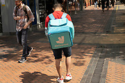 Deliveroo delivery rider / courier in the city centre on 14th June 2021 in Birmingham, United Kingdom. Deliveroo is an online food delivery company founded by William Shu in 2013 in London, England.