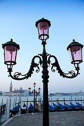 Ornate lamps and gondolas moored at San Marco before dawn in Venice Italy