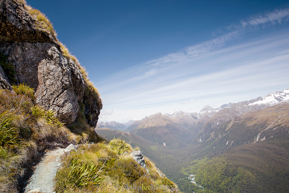 Scenic landscape with view of a footpath, a cliff and snowcapped mountains in the background, Routeburn Track, South Island, New Zealand