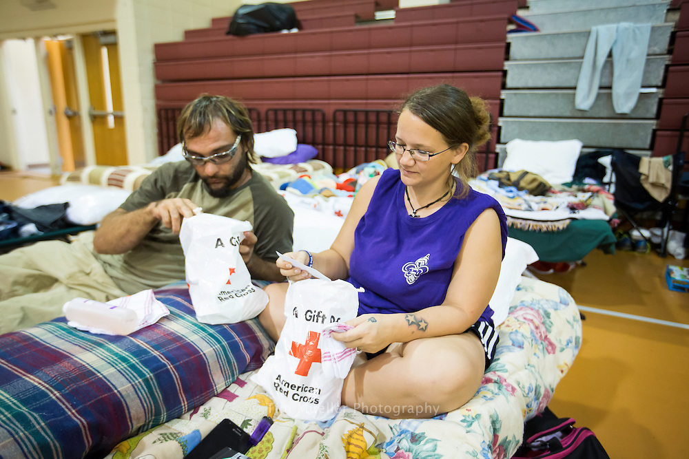 Anthony and Brandi Estrada check out Red Cross gift bags Wednesday, August 17, 2016 as they take shelter at the North Park Recreation Center shelter in Denham Springs, La.