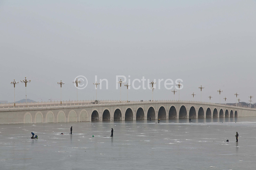Residents fish on a frozen lake in Yinchuan, Ningxia Hui Autonomous Region, China on 21 December  2012.  With its dry climates and ample sunshine, and encouraged by the huge boom in Chinese consumer's demand for wine, Ningxia is quickly becoming one of the biggest wine producing regions in China.
