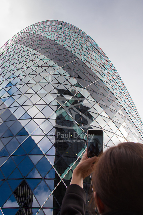 London, September 7th 2015. PICTURED: A woman takes a picture withy her phone as the Gerkhin's Property Manager Jimmy Demetriou abseils down the face of the building he manages.  The Outward Bound Trust City Three Peaks Challenge in conjunction with The Royal Navy and Royal Marines Charity is a breathtaking abseiling endeavour on the greatest urban mountain range: The City of London.