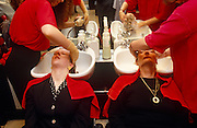 Two smart businesswomen sit side-by-side with both their heads tilted back into two sinks in a City of Londopn hair salon and enjoy the pampering of a shampoo and re-styling. With matching red towels over their shoulders to ensure their clothing is kept dry, the ladies keep their eyes closed and relax as two paiurs of hands from two stylists massage the shampoo into their scalps. We also see the scene reversed, relfected in the mirror, an the echo of everything just mentioned.