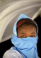 Corail Cesselesse is the name of the government relocation camp in Haiti with over 5,000 earthquake victims living in tents on June 30, 2010. Here, camp resident Claudina Derozin, 17, covers her face to ward off the dust as she sits  under the shade of her tent..***For Fred Grimm package on July 11***