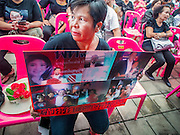 12 OCTOBER 2104 - BANG BUA THONG, NONTHABURI, THAILAND: A Red Shirt supporter holds up pictures of deposed Prime Minister Yingluck Shinawatra at the funeral rites for Apiwan Wiriyachai at Wat Bang Phai in Bang Bua Thong, a Bangkok suburb, Sunday. Apiwan was a prominent Red Shirt leader, member of the Pheu Thai Party of former Prime Minister Yingluck Shinawatra, and a member of the Thai parliament. The military government that deposed the elected government in May, 2014, charged Apiwan with Lese Majeste for allegedly insulting the Thai Monarchy. Rather than face the charges, Apiwan fled Thailand to the Philippines. He died of a lung infection in the Philippines on Oct. 6. The military government gave his family permission to bring him back to Thailand for the funeral. He will be cremated later in October. The first day of the funeral rites Sunday drew tens of thousands of Red Shirts and their supporters, in the first Red Shirt gathering since the coup.    PHOTO BY JACK KURTZ