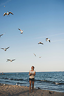 Odessa, Ukraine - September 15, 2016: A gull is moments away from grabbing a piece of bread thrown into the air by a woman on the beach in Odessa.