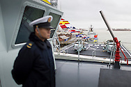 A sailor stands guard aboard the Chinese Naval assault ship Chang Bai Shan at Portsmouth Royal Navy Base today. The ship is involved in the first visit by the Chinese Navy to the UK since 2007 and the largest ever. She is accompanied by the frigate Yun Cheng (in distance) and the replenishment ship Chaohu. The ships arrived in Portsmouth 24 hours early due to the expected bad weather. The Royal Navy statement stated that the five day formal visit is aimed at enhancing military understanding between the UK and China. Picture date Monday 12th January, 2015.<br /> Picture by Christopher Ison. Contact +447544 044177 chris@christopherison.com