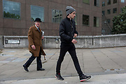 A city gent wearing a traditional but now a very rarely-seen bowler hat walks towards London Bridge rail station with a youth wearing a woolen hat and earphones, on 6th June 2017, on London Bridge, in the south London borough of Southwark, England. The griffin behind him is on the southern end of the Thames crossing but marks the southern boundary of the City of London, the capitals financial district.