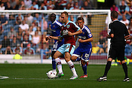 Scott Arfield of Burnley passes the ball under pressure from Konstantin Kerschbaumer of Brentford. Skybet football league championship match, Burnley  v Brentford at Turf Moor in Burnley, Lancs on Saturday 22nd August 2015.<br /> pic by Chris Stading, Andrew Orchard sports photography.