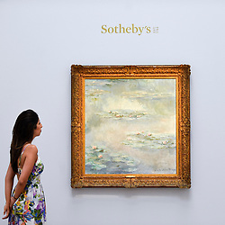 """© Licensed to London News Pictures. 14/06/2019. LONDON, UK. A staff member views """"Nymphéas"""", 1908, by Claude Monet (Est. £25-30m). Preview of Impressionist and Modern art sales, which will take place at Sotheby's New Bond Street on 18 and 19 June 2019.  Photo credit: Stephen Chung/LNP"""