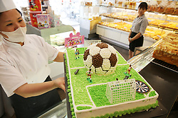 June 25, 2018 - Nantong, China - A baker makes a World Cup-themed cake at a bakery in Nantong, east China's Jiangsu Province. The cake is complete with a football, players, goals and a football field. (Credit Image: © SIPA Asia via ZUMA Wire)