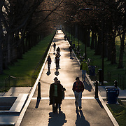 The low morning sun casts long shadows from walkers along the new walkway next to the Lincoln Memorial Reflecting Pool in Washington DC.