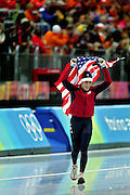 U.S. speed skater Chad Hedrick of Spring, Texas runs with the U.S. flag after winning the silver medal during the Men's 10,000 Meter Speed Skating event at the Oval Lingotto in Turin, Italy on Friday February 24, 2006. Bob de Jong of the Netherlands won the event with a time of 13:01.57 while U.S. speed skater Chad Hedrick took the silver with a time of 13:05.40 and Carl Verheijenof alsoo of the Netherlands took the bronze with a time of 13:08.80..(Photo by Marc Piscotty / © 2006)