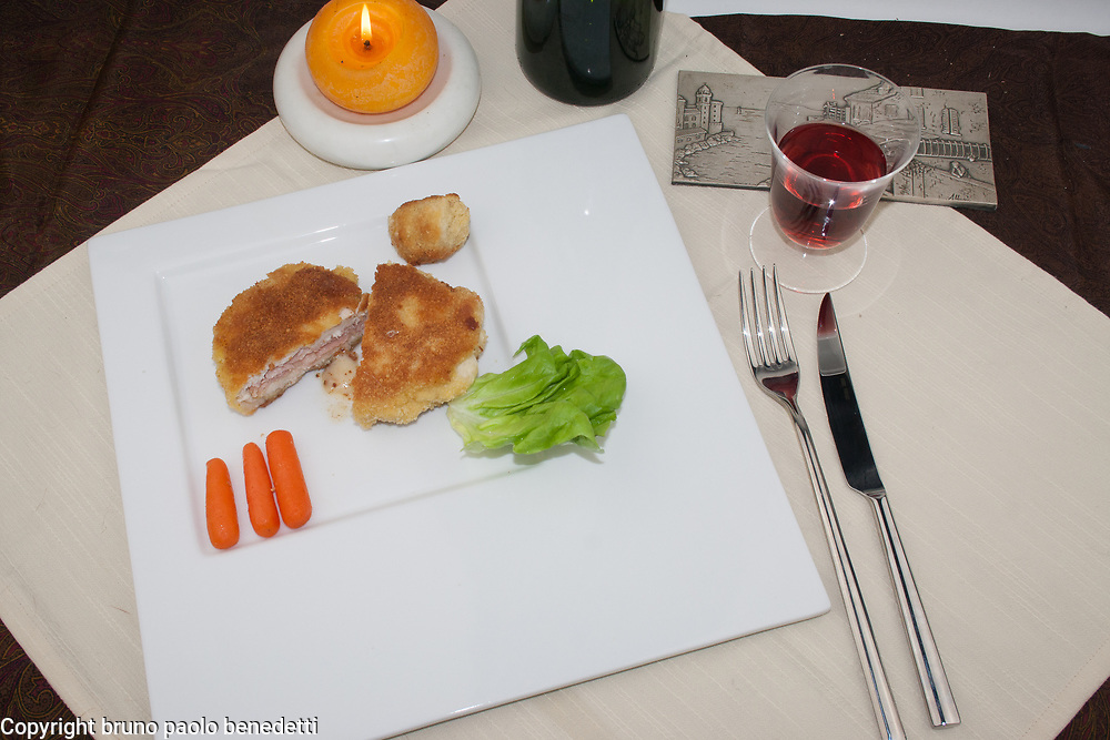cordon bleu fried filled chicken breast plating side view from above presentation on white dish with garnish, fork, knife, red wine and candle
