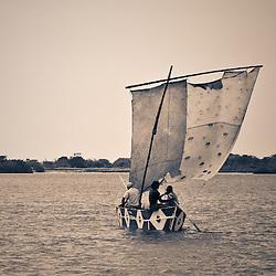 Barco a vela e pescadores artesanais no Mussulo ao final do dia. Angola