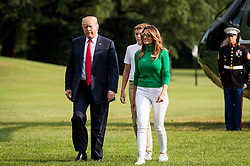 President Donald Trump glances over at the press as he walks across the South Lawn from Marine One with First Lady Melania Trump and his son Barron, after returning to the White House on Aug. 19, 2018 in Washington, D.C. President Trump was returning from the weekend at his Bedminster, New Jersey golf resort. Photo by Pete Marovich/AbacaPress/Pool