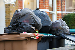 © Licensed to London News Pictures. 28/12/2020. London, UK. Bags of rubbish are gathered on top of bins in a front garden in London after the festive period. Photo credit: Dinendra Haria/LNP