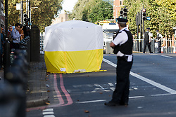 © Licensed to London News Pictures. 22/09/2016. LONDON, UK.  A Police officer looks at the forensic tent at the scene. A man was found dead in the street following a suspected assault, near All Saints DLR station just before midnight last night.  Photo credit: Vickie Flores/LNP