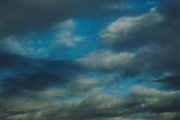 A mixture of cloud formations and their hues create this dramatic blue sky.